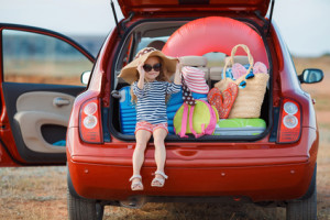 Little girl in straw hat sitting in the trunk of a car