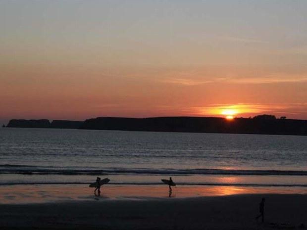 Die zwei letzten Surfer kommen während des Sonnenuntergangs aus den Wellen