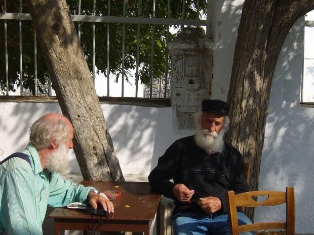 Zwei griechische Männer sitzen am Tisch und unterhalten sich