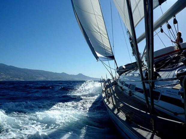 Blick auf Meer und Insel vom Deck der Yacht bei sportlichem Segeln