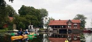 Seekajakgruppe vor einem alten Haus
