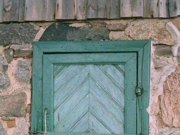 Eine grüne Tür führt in ein altes Backsteinhaus
