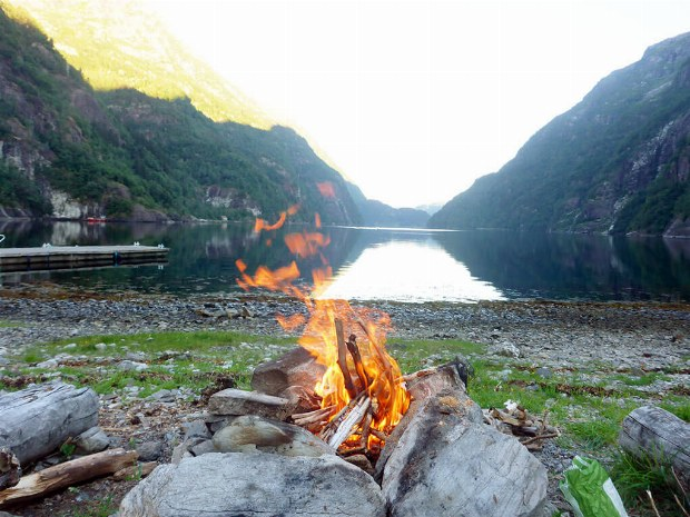 Lagerfeuer am Ufer mit Blick auf den Fjord