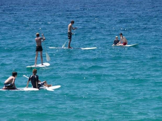 Jugendliche auf dem Meer in Korsika beim Stand up paddling
