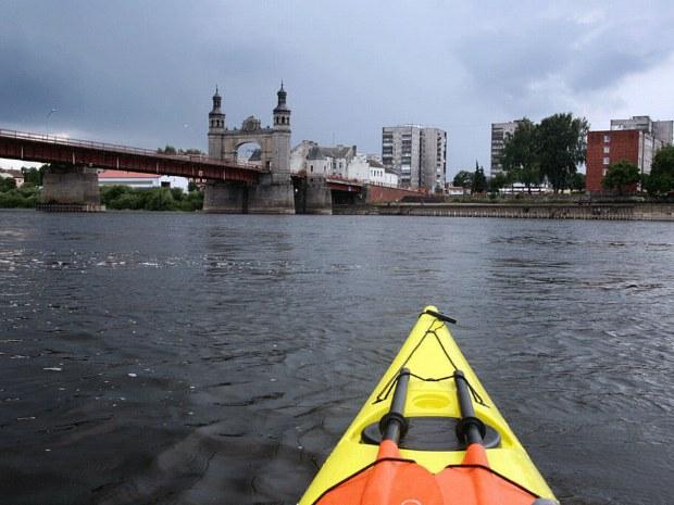 Seekajak im Fluss vor einer Stadt und einer Brücke