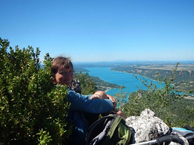 Wanderin macht Pause an einem Aussichtspunkt mit Blick auf den Lac de Ste. Croix
