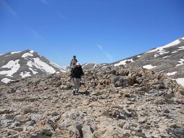 Auf Steinwegen gehen zwei Urlauber den Berg hinab