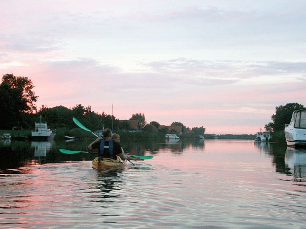 Gäste paddeln entlang der Ufer im Sonnenuntergang