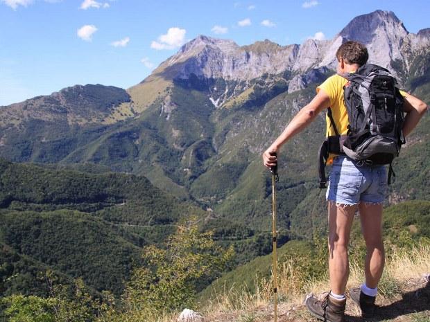 Ein Mann steht an der Kante des Berges und schaut ins Tal