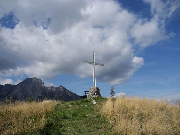 Auf der Bergspitze sieht man eine Bank und ein Kreuz