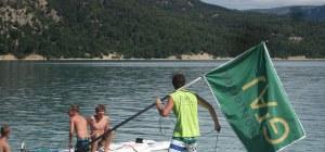 Kinderbetreuung auf dem Lac de Ste. Croix. Jugendliche auf Surfbrettern und Teamer mit Fahne.