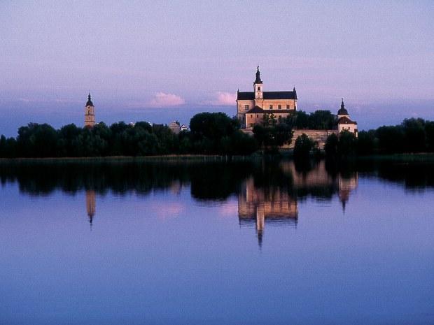 Eine Burg an einem See erglänzt im abendlichen Licht