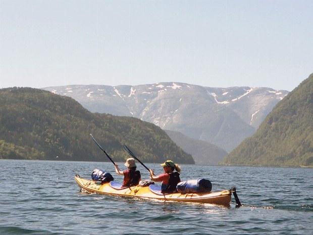 Zwei Gäste paddeln im Wasser entlang von Bergen