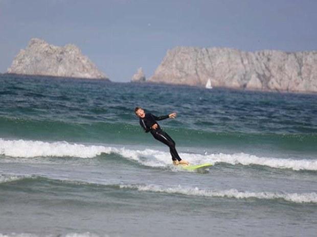 Junger Wellenreiter verliert soeben das Gleichgewicht und fällt ins Wasser.