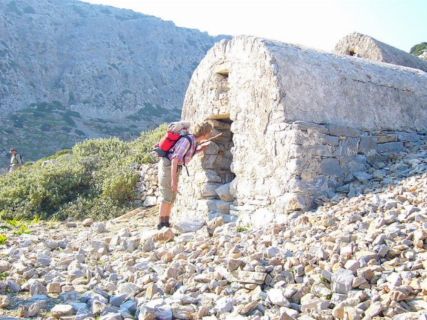 Ein Mann schaut in ein kleines verlassenes Steinhaus