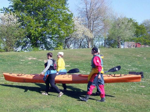 Gäste tragen ein Seekajak über ein Wiese