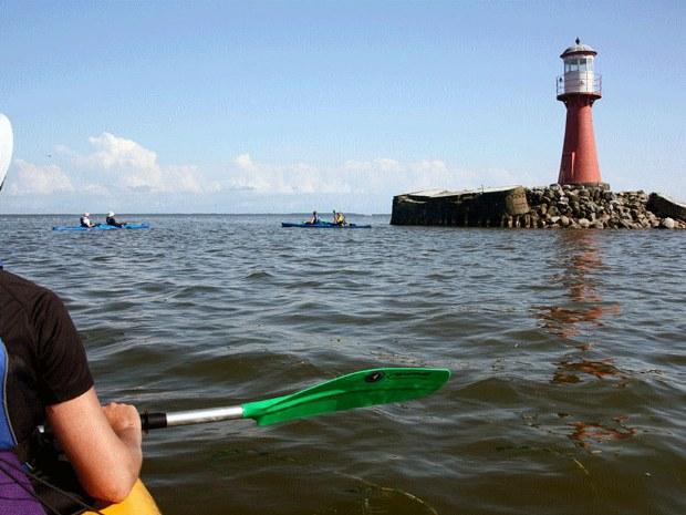 Seekajakfahrer rund um einen roten Leuchtturm