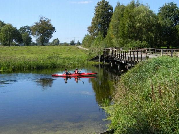Zwei Kanufahrer paddeln unter einer Brücke her