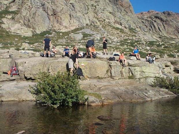 Wandergruppe macht Pause an einem Fluss in den Bergen von Korsika