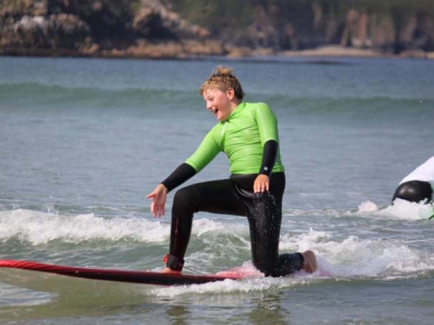 Junge übt Wellenreiten auf kleiner Welle im Surfcamp