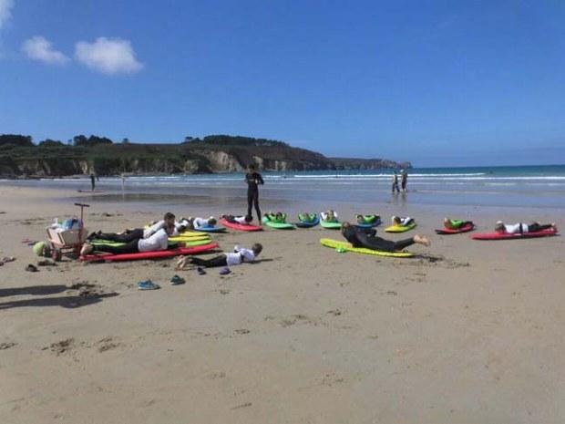 Surfgruppe bekommt erste Übungen am Strand gezeigt