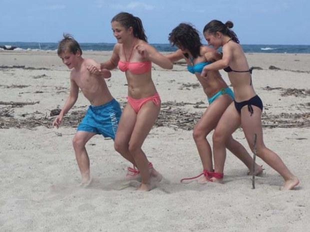 Jugendliche bei einem Strandspiel während einer Strandrallye