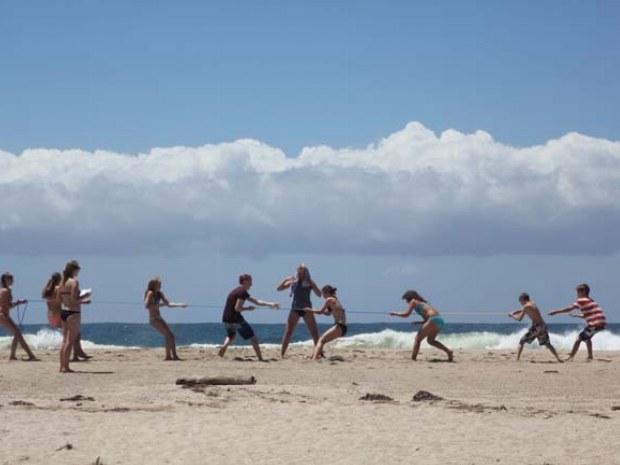Teenager messen ihre Kräfte beim Tauziehen am Strand