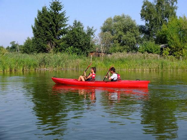 Zwei Jungen fahren ein Kanu auf dem See