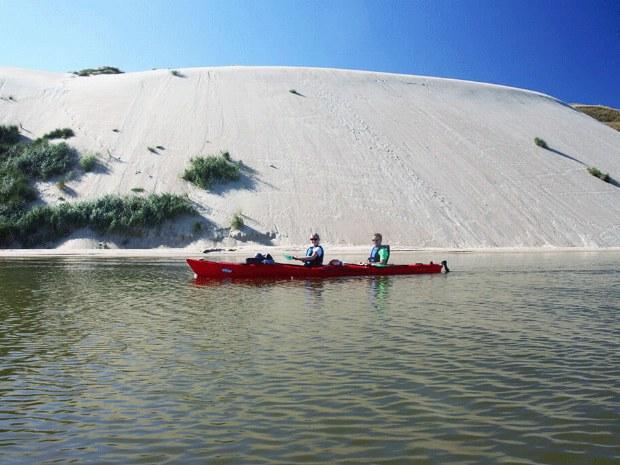 Gäste im Seekajak vor den hohen Dünen