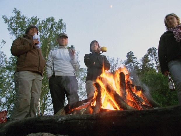 Gruppe steht um ein Lagerfeuer mit warmen Getränken