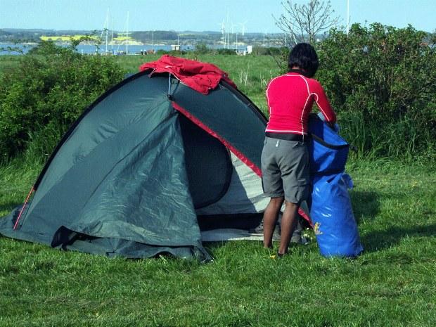 Ein Gast baut ein Zelt am Ufer auf